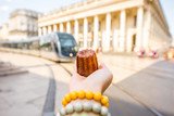 Holding a traditional Bordeaux sweet cake called Canele outdoors on the street near the Grand theatre building in Bordeaux - 163780781