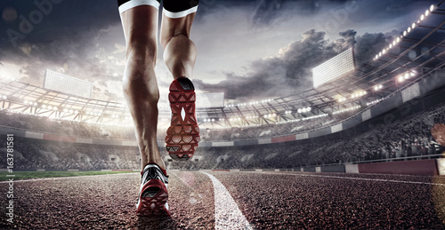 Sports background. Runner feet running on stadium closeup on shoe. Dramatic picture.