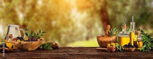 Świeżo zebranych oliwek jagody w miski z drewna i olej prasowany w szklanych butelkach