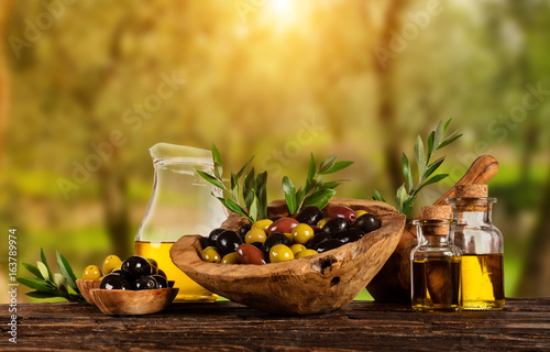 Freshly harvested olives berries in wood bowls and pressed oil in glass bottles - 163789974