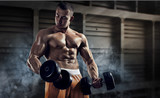 Sport and fitness. Muscular bodybuilder in the gym training with dumbbells - 163792341