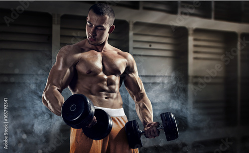 Sport and fitness. Muscular bodybuilder in the gym training with dumbbells