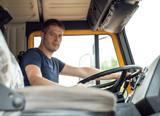 Male trucker in cabin of his yellow truck. - 163795190