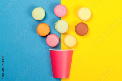 Colorful macaroons falling into red paper cup. Minimal concept. Appetizing macaroons on blue and yellow background. Photo by volurol