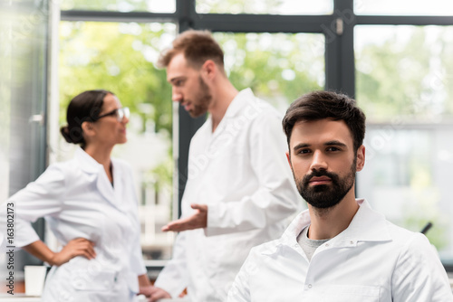 Plakát Bearded young scientist looking at camera while colleagues talking behind
