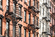 New York City style apartment buildings exterior view with windows and fire escapes