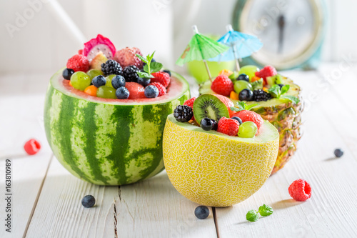 Fruits salad in melon and pineapple with berry fruits - 163810989