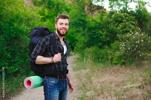 Young Man Traveler with backpack relaxing outdoor. Summer vacations and Lifestyle hiking concept