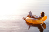 Business woman working on a laptop in an inflatable ring in the water, a copy of the free space. Workaholic, work on vacation. - 163818795