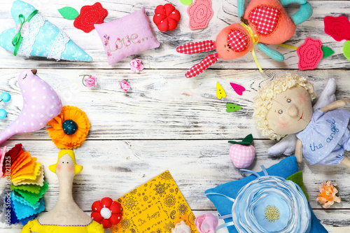 Many bright colored soft textile fabulous toys and things handmade greeting card and ceramic plate. Workplace needlewoman and creative person. Flat lay, top view.