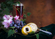 Glass of wine, pink flowers, grapes and lemon