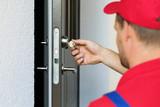 door lock service - locksmith working in red uniform - 163825971