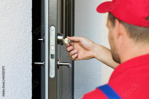 door lock service - locksmith working in red uniform Poster