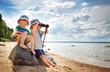 Leinwandbild Motiv Babygirl and babyboy sitting on the beach