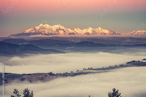 panorama over misty Spisz highland to snowy Tatra mountains in the morning, Poland and Slovakia landscape
