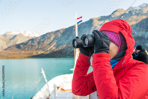 Tourist looking at Alaska Glacier Bay landscape using binoculars on cruise ship. Woman on vacation travel looking for wildlife enjoying cruising famous tourist destination.