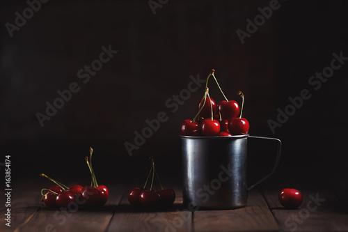 Cherries in metal mug on table on dark background, toned image