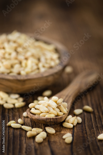 Portion of Pine Nuts on wooden background (selective focus) - 163863506