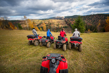 View from quad bike with four men at ATV in front on the top of hill. Beautiful landscape of rolling countryside and colorful forest under the sky with cumulus clouds in autumn