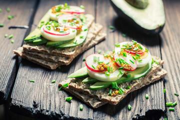 Closeup of tasty sandwich with avocado, eggs and radish