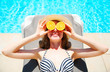 summer holidays concept - woman holds in hands oranges and hides his eyes on blue water pool background