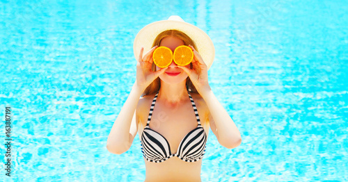 Summer sunny portrait woman holds in hands oranges hides his eyes on blue water pool background - 163887191