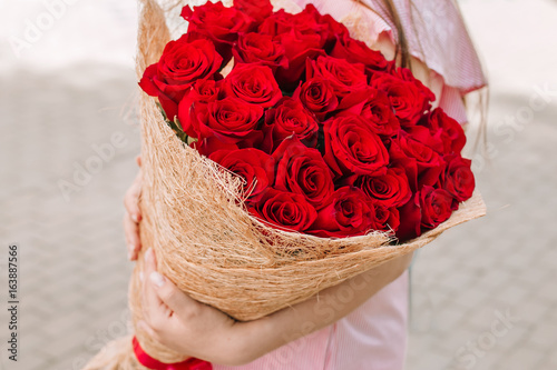 Bouquet of red roses in the hands of a woman