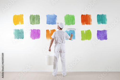 Rear view of painter man who make and chooses from various color samples isolated on the big blank white wall