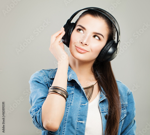 Young Beautiful Woman in Denim Outfit Enjoying the Music and Looking Up