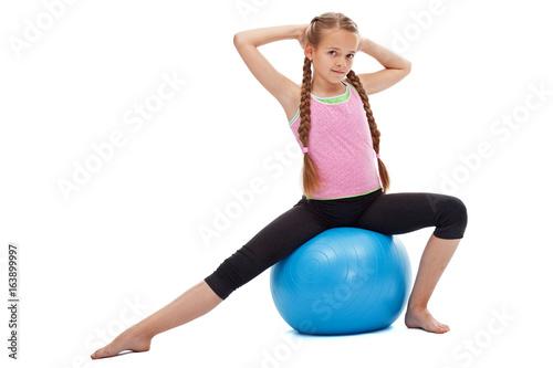 Little girl sitting on large rubber ball exercising