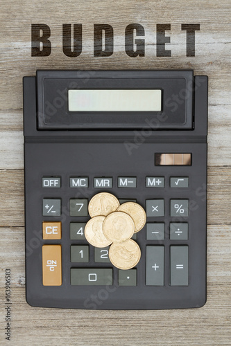 Calculator with a gold dollar coin on weathered wood - 163906583