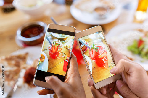hands with drinks on smartphones at restaurant - 163908185