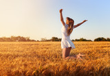 Beautiful young girl in white dress jumping in golden wheat - 163924902