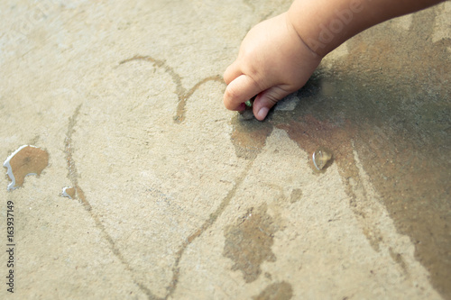 baby hand drawing heart by ice cube