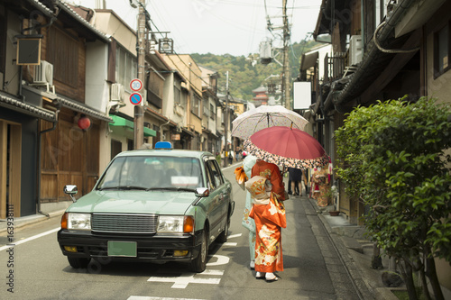 Vintage street scene in Kyoto province, Japan with taxi car and females wearing Yukata and handling traditional umbrellas.