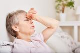 Seniorin mit Kopfschmerzen liegt im Bett - 163938576