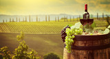 Red wine bottle and wine glass on wodden barrel. Beautiful Tuscany background - 163938915