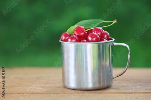 Cherries in iron cup on table