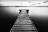 Black and white landscape. Wooden walkway in the sea and surface of smooth water. Marsala, Sicily