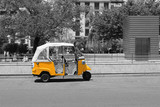 Fototapety Black and white picture of tuk tuk small passenger three weel mini car isolated on summer empty street road background. Bright yellow rickshaw helps tourists to travel around the city fast