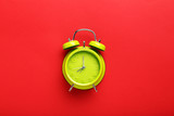 Green alarm clock on the red background - 163962996