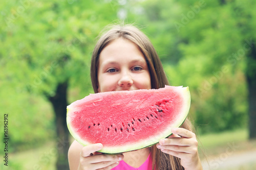 Portrait of  little girl with slice of watermelon in the park Poster