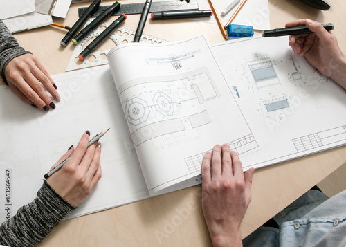 Designers hands drawing scheme of piece of furniture on creative desk top view Poster