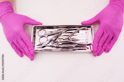 Plexiglas Manicure Manicure professional tools closeup on white background. Nailcare instrument in beautician's hands top view with copy space.