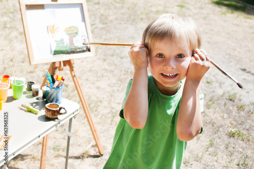 Little boy draws a drawing with brushes