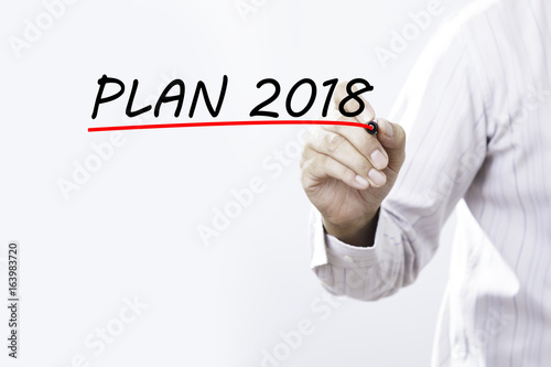 Poster Businessman hand writing plan 2018 with red marker on transparent wipe board, bu