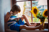 Cute little toddler child, playing on tablet on a window - 164008931