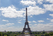 Eiffel tower against blue sky with clouds