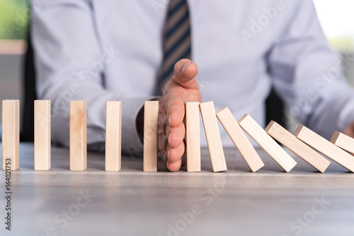 Concept of business control by stopping domino effect - 164021753