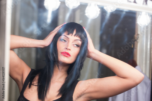 Young woman trying fit wig in mirror Poster